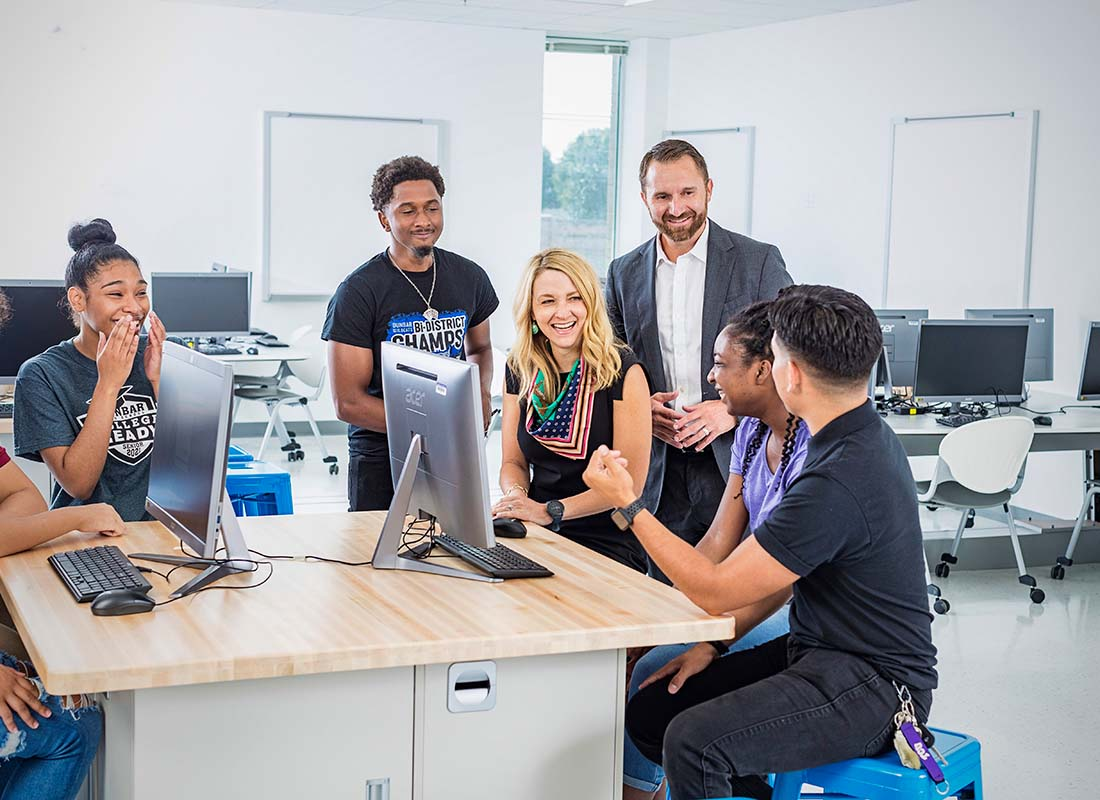 teacher and class around computer